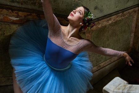 photograph of a woman in bright blue tutu and toe shoes en pointe on a marble staircase with with dull, cracked green painted walls behind her