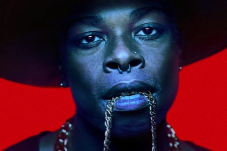 close-up photograph of a man wearing a wide-brimmed hat with a gold chain hanging from his mouth in front of a bright red background